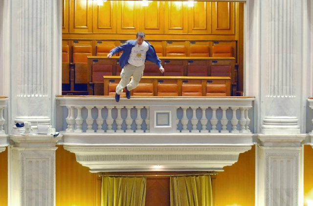 Adrian Sobaru, an electrician at the national television station, throws himself from a balcony in Romania's Parliament in protest against cuts of civil servant pay. AP Photo/Bogdan Stamatin/Mediafax Foto, 2010