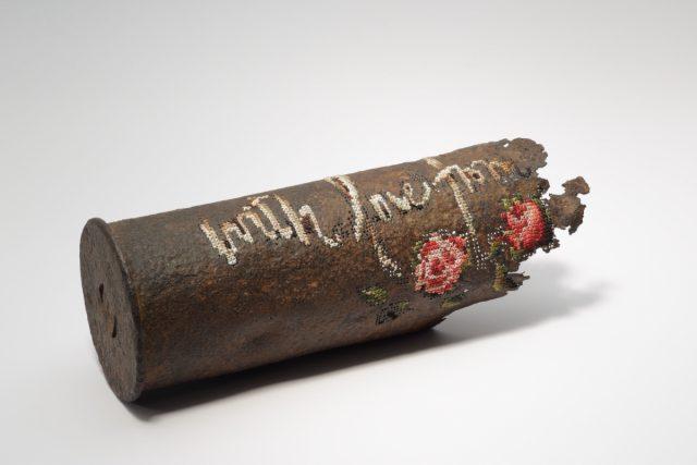 """""""With Love from..."""". 2018.  Zenitinio pabūklo """"8,8 cm FlaK"""" sviedinio tūtos fragmentas (II-ojo pas. karo). Siuvinėjimas kryželiu, gręžima. / 8.8 cm FlaK anti-aircraft gun shell from WWII.  Cross stitch embroidery, drilling. Photo by Modestas Ežerskis"""